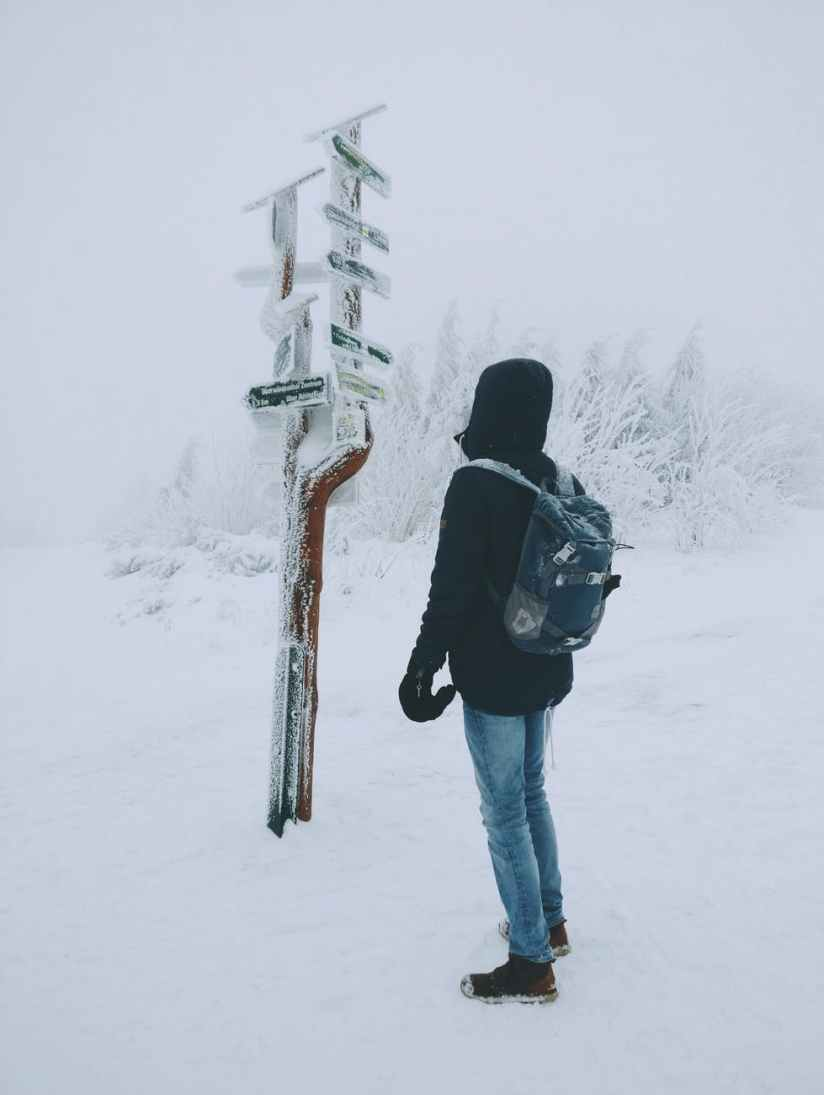 person wearing black hoodie and blue denim jeans standing over frozen arrow signage over snow ground
